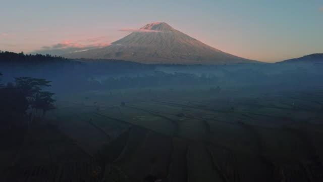 vidéos et rushes de vue aérienne du champ de riz de terrasse de paysage du volcan de mont agung à bali en indonésie - chaîne de montagnes
