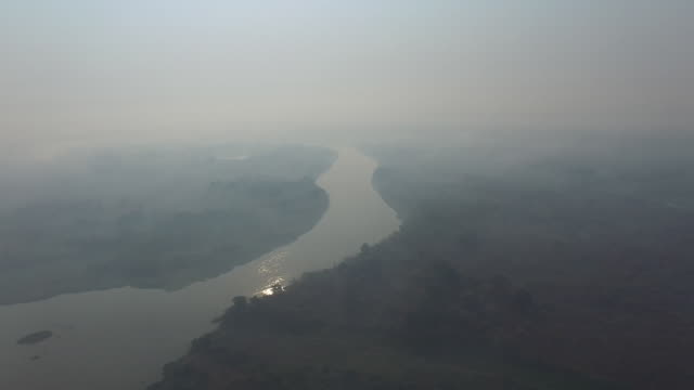 stockvideo's en b-roll-footage met aerial view of landscape with river and fields covered with smoke after fires in sao braz farm, at transpantaneira road, 15 km of porto jofre city at... - number 9