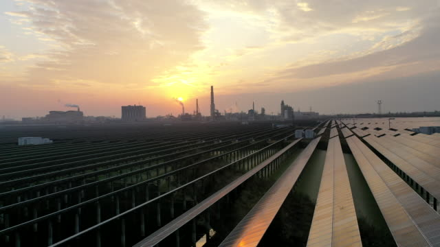 aerial view of large area solar power plant at sunset with chemical plant in the distance - power line点の映像素材/bロール