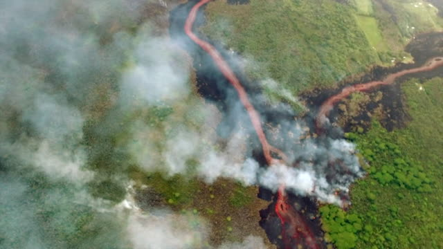 vídeos de stock e filmes b-roll de aerial view of lava flow caused by hawaii's kilauea volcano eruption - kauai