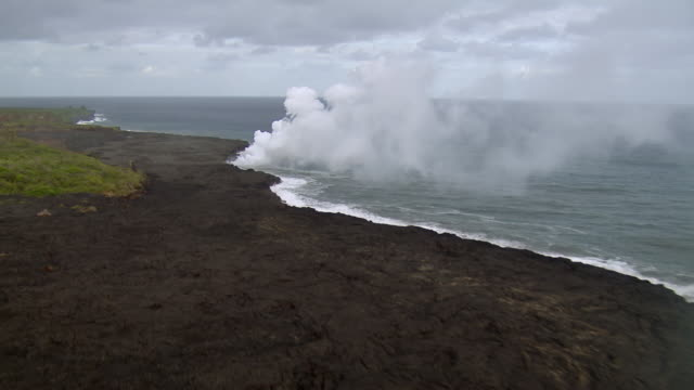 aerial view of lava flow meeting pacific ocean from kilauea volcano on the big island of hawaii. - big island hawaii islands stock videos & royalty-free footage