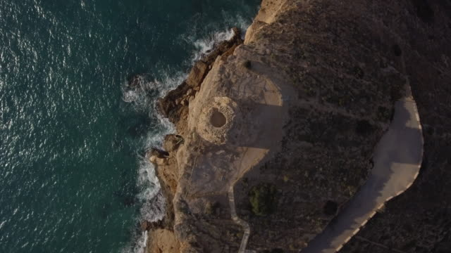 stockvideo's en b-roll-footage met aerial view of les caletes tower or seguró is a defensive tower of the sixteenth century that is located in punta de las caletas or punta del cavall  in the municipality of benidorm (alicante, spain) - 16e eeuwse stijl