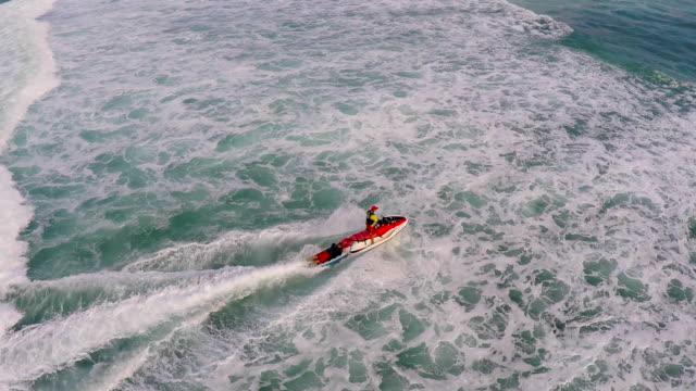 stockvideo's en b-roll-footage met aerial view of lifeguard surf rescue jet ski personal watercraft in hawaii. - badmeester