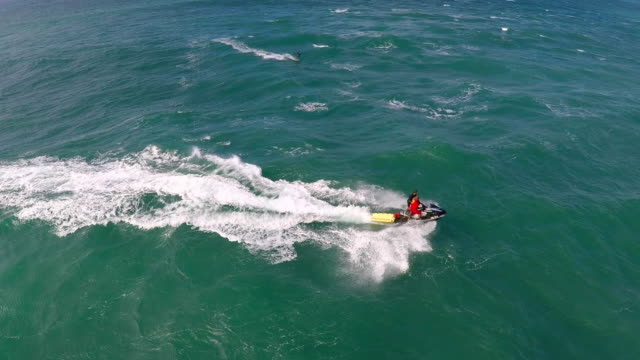 aerial view of lifeguard surf rescue jet ski personal watercraft in hawaii. - slow motion - bagnino video stock e b–roll
