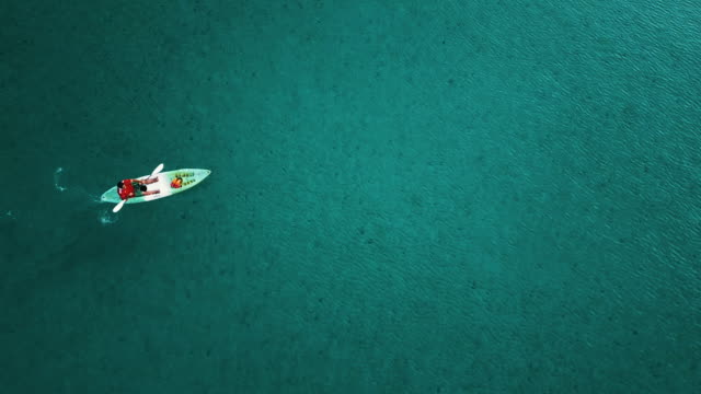 vídeos de stock e filmes b-roll de aerial view of lonely canoe in sea at thailand. - kayaking