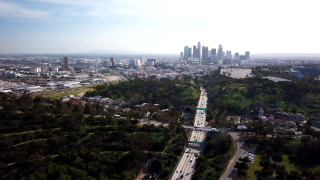 4k aerial view of los angeles freeway and skyline with traffic and tunnels - hollywood sign stock videos & royalty-free footage