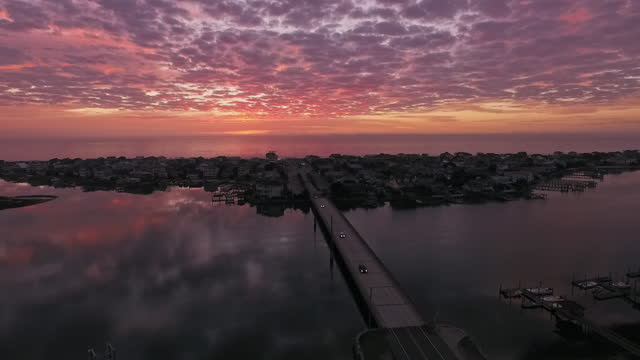 drone. aerial view of luxury beach houses during spectacular pink sunrise at wrightsville beach as cars drive over the bridge - new orleans stock videos and b-roll footage
