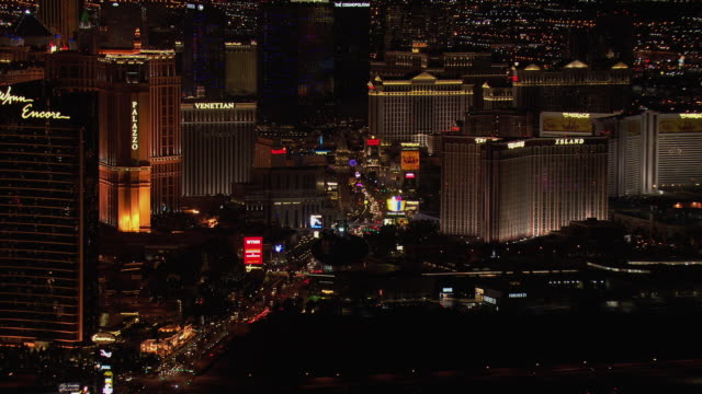 aerial view of luxury hotels and casinos on the las vegas strip at night in downtown las vegas, nevada, united states of america. - the palazzo las vegas stock videos & royalty-free footage