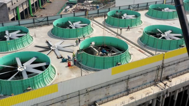aerial view of maintenance worker during mechanical work on cooling tower at power plant - cooling tower stock videos & royalty-free footage