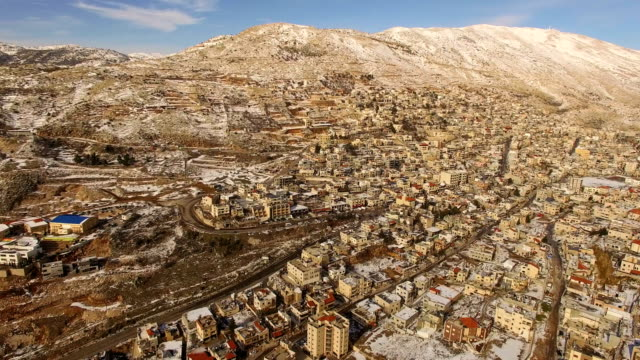 aerial view of majdal shams druze village, with golan heights covered with snow - syrien stock-videos und b-roll-filmmaterial