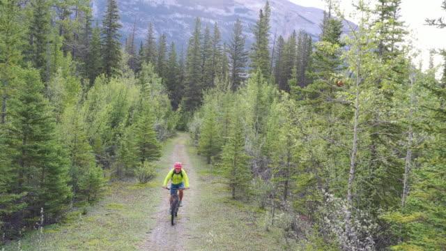 luftaufnahme eines männlichen mountainbikers, dem weg bei sonnenaufgang folgend - mountainbiking stock-videos und b-roll-filmmaterial