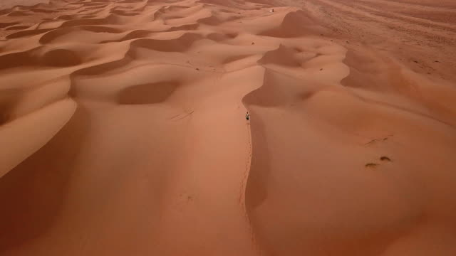 Aerial view of male running across dunes in desert at sunrise