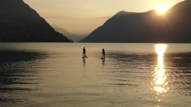 luftaufnahme von mann und frau paddeln boarding auf see bei sonnenaufgang aufstehen - surfbrett stock-videos und b-roll-filmmaterial