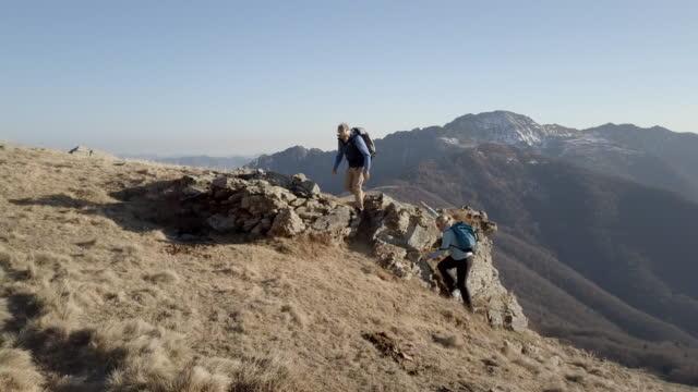 luftaufnahme der mann hilft frau bis zum aussichtspunkt - berggipfel stock-videos und b-roll-filmmaterial