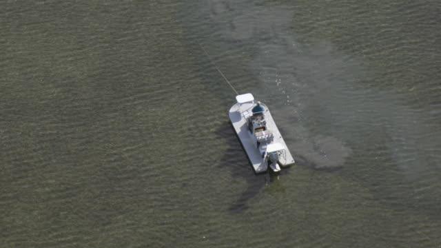 vídeos y material grabado en eventos de stock de aerial view of man in a boat fishing in the laguna madre water near port mansfield, texas. - menos de diez segundos
