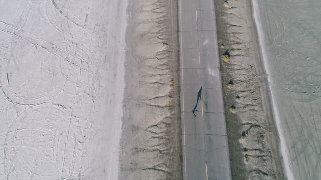 Aerial view of man longboarding along empty road
