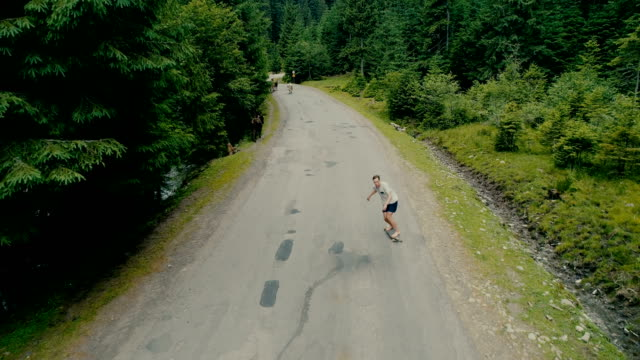 Aerial view of  man long-boarding in the Carpathian mountains