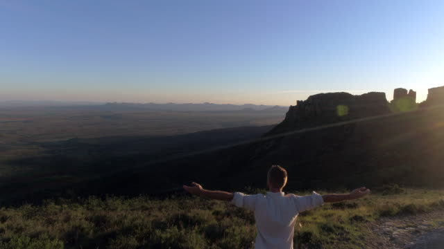 aerial view of man reaching mountain top - arms outstretched stock videos & royalty-free footage