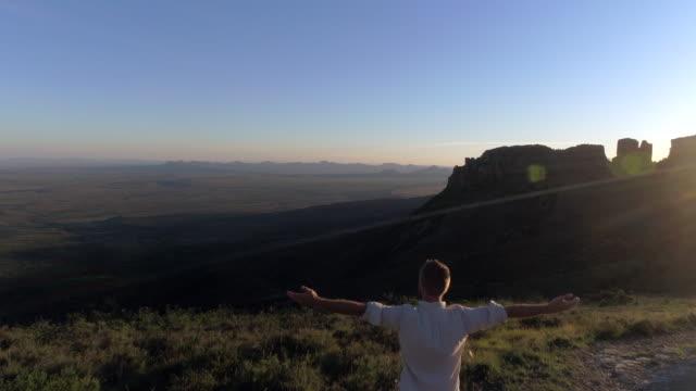 vidéos et rushes de vue aérienne de l'homme pour atteindre le sommet de la montagne - les bras écartés