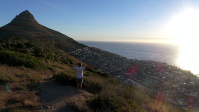 aerial view of man reaching mountain top - lion's head mountain stock videos and b-roll footage
