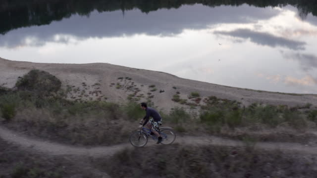 aerial view of man riding a bicycle near lake at sunset - mountain bike stock videos & royalty-free footage