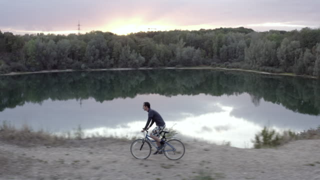 aerial view of man riding a bicycle near lake at sunset - triglia tropicale video stock e b–roll