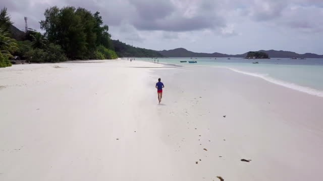 Aerial view of man running on tropical beach in Seychelles