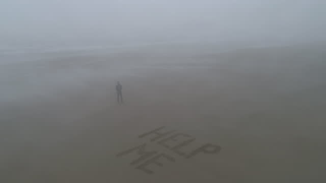 "aerial view of man standing beside ""help me"" sign on beack - western script stock videos & royalty-free footage"