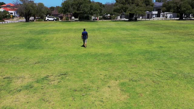 aerial view of man walking alone in the park - leisure activity stock videos & royalty-free footage