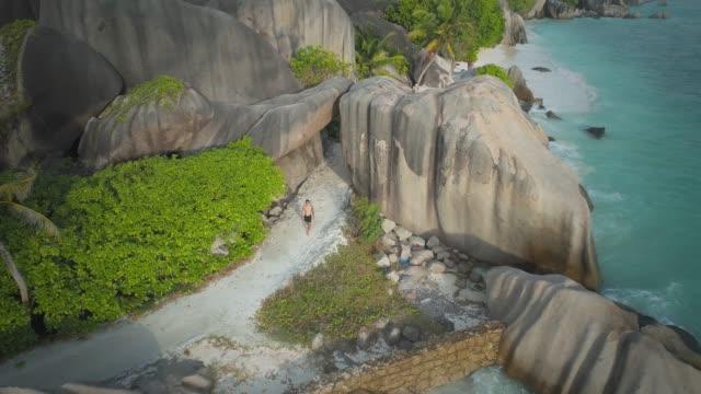 aerial view of man walking through anse source d'argent, la dique seychelles - drone 4k - seychelles stock videos & royalty-free footage