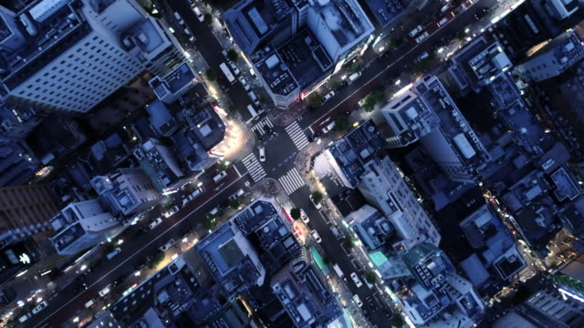 aerial view of many buildings and huge crossroad - イルミネーション点の映像素材/bロール