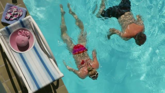 luftaufnahme des reifen paares, das im pool schwimmt - schwimmbeckenrand stock-videos und b-roll-filmmaterial