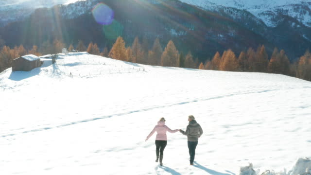 vidéos et rushes de aerial view of mature couple walking through snowy meadow in mountains - italie