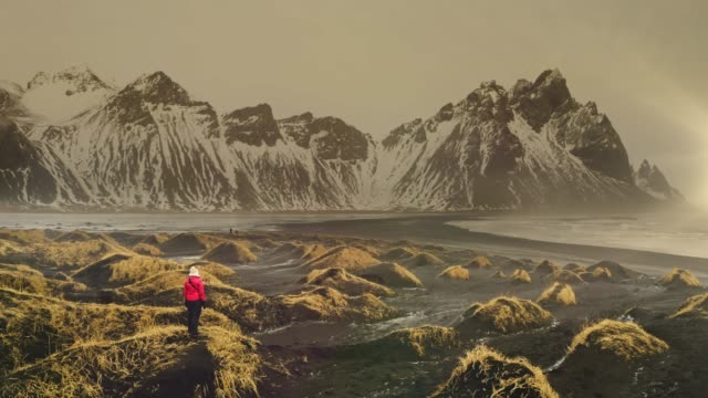 aerial view of mature woman exploring vestrahorn mountains near the sea - mountain peak stock videos & royalty-free footage