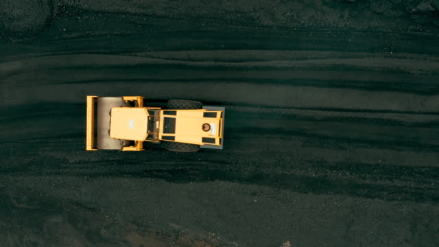 vídeos de stock e filmes b-roll de aerial view of mechanical digger in coal mining area - pedreira