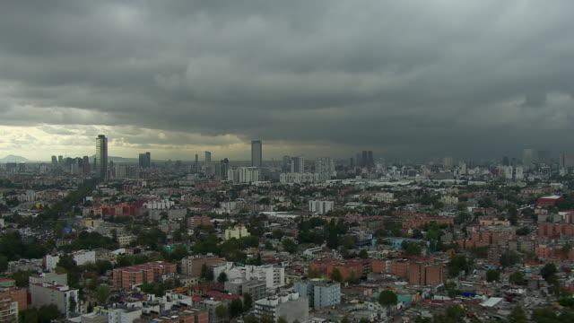 vídeos de stock, filmes e b-roll de aerial view of mexico city with approaching storm off in the distance. - expansão urbana