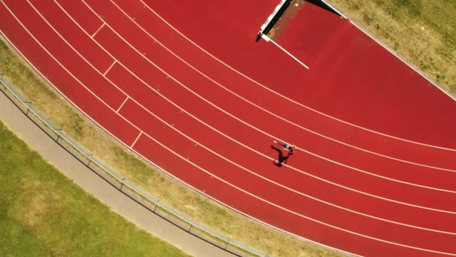 aerial view of mid adult female athlete running around track - less than 10 seconds stock videos & royalty-free footage