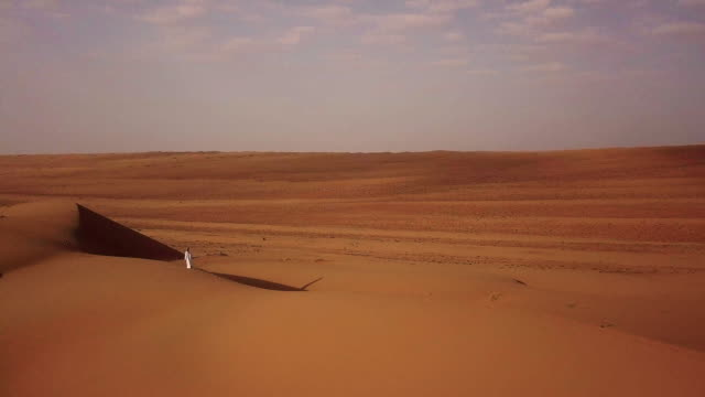 Aerial view of Middle Eastern man walking over dunes in desert at sunrise