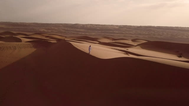 stockvideo's en b-roll-footage met aerial view of middle eastern man walking over dunes in desert at sunrise - midden oosten