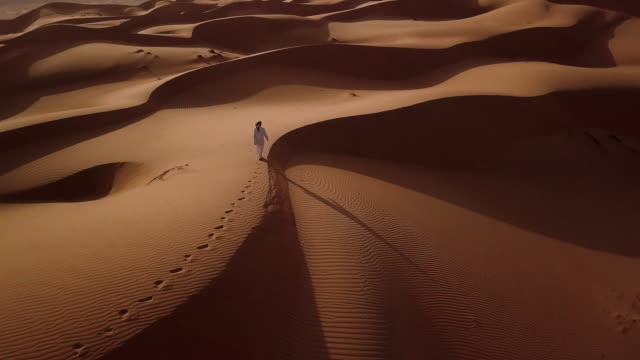 vidéos et rushes de aerial view of middle eastern man walking over dunes in desert at sunrise - dune de sable