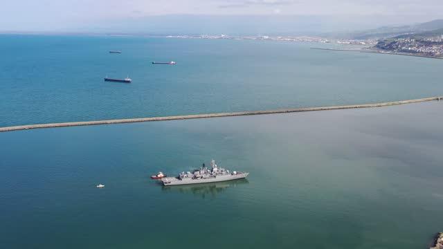 luftaufnahme eines militärkriegsschiffes, das sich einem handelshafen nähert. - war stock-videos und b-roll-filmmaterial