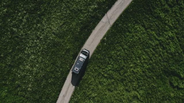 vídeos de stock e filmes b-roll de aerial view of mini van on road in remote location - carrinha veículo