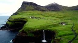 Aerial view of Múlafossur waterfall near a small village, Faroe island.