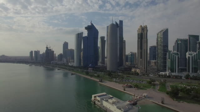 aerial view of modern buildings by sea against cloudy sky, doha, qatar - doha stock videos & royalty-free footage