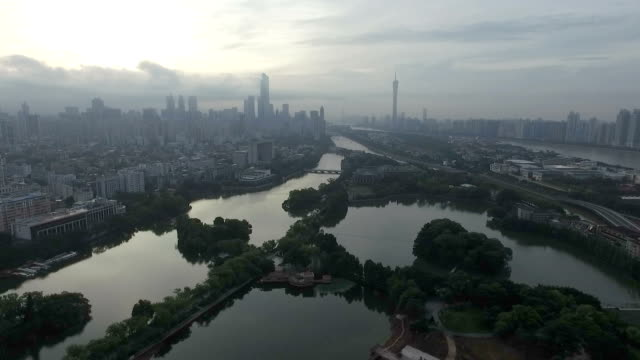 aerial view of modern city with long river in cloud sky
