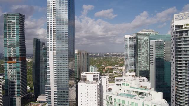 vidéos et rushes de vue aérienne des tours modernes et des gratte-ciel à brickell, downtown miami, sur le front de mer.  clip vidéo réalisé par drone avec mouvement de la caméra de forwarding. - miami
