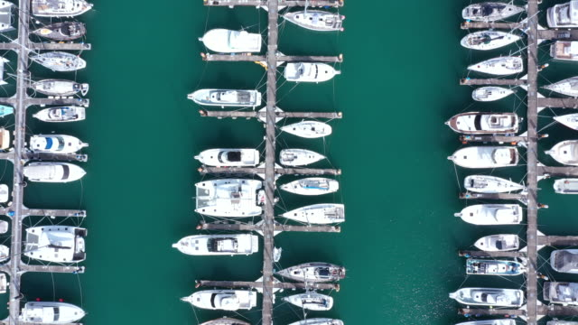vídeos de stock e filmes b-roll de aerial view of moored boats in harbor - docas