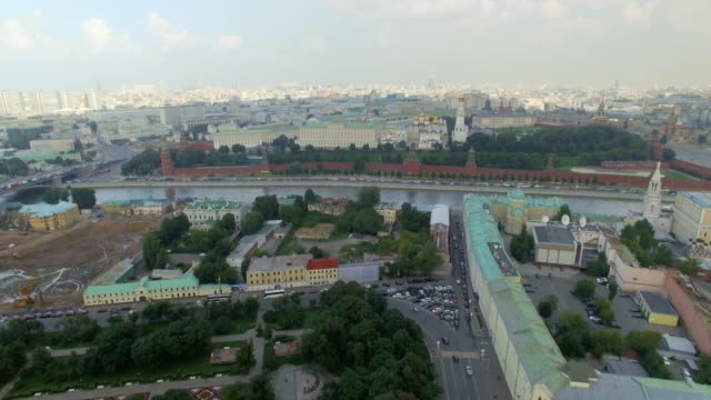 Aerial view of Moscow with Vehicles moving  past Kremlin Wall, along Moskva River.