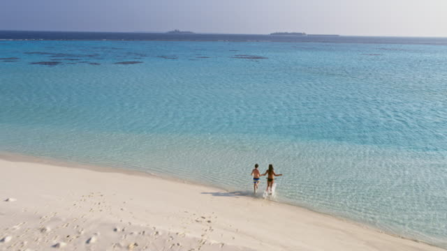 Aerial view of mother and boy on a tropical beach running, Maldives