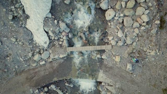 luftaufnahme der mountainbiker über schmale brücke über gletscherfluss in alpen - sicherheitsmaßnahme stock-videos und b-roll-filmmaterial